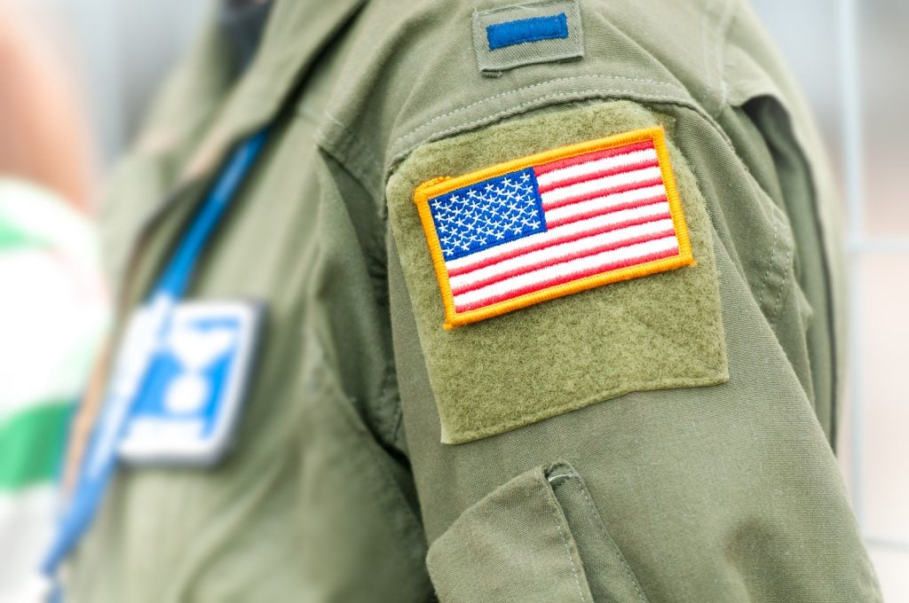 Part of uniform of United States Air Force. Person wearing military clothes with pockets and national symbol. Focus on american flag in yellow frame attached to shoulder part of army clothing. ** Note: Shallow depth of field